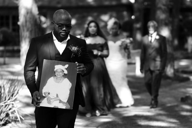 Leading the wedding procession, Eyram's brother carries a photograph of their deceased mother into the wedding chapel.